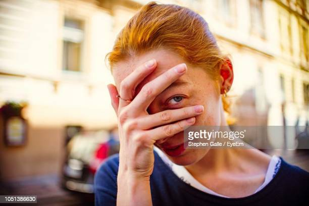 close-up portrait of young woman with hand covering face standing on street - covering stock pictures, royalty-free photos & images