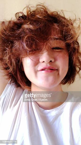 close-up portrait of young woman with messy hair at home - imperfection stock pictures, royalty-free photos & images