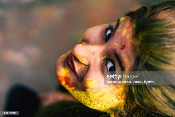 Close-Up Portrait Of Young Woman With Powder Paint On Face During Holi