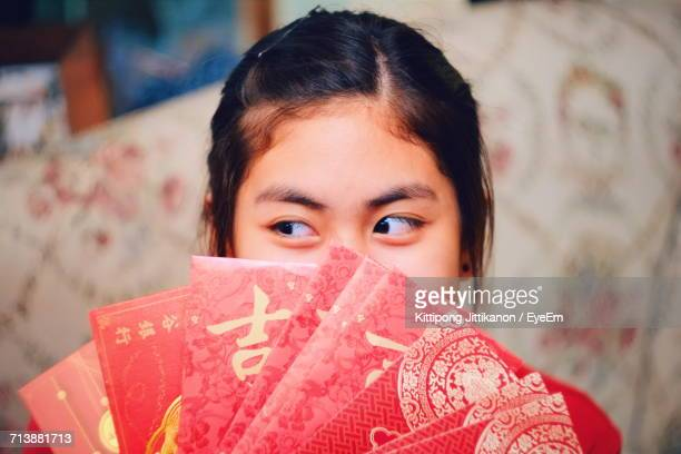 close-up portrait of young woman with red envelopes - chinese new year stock pictures, royalty-free photos & images