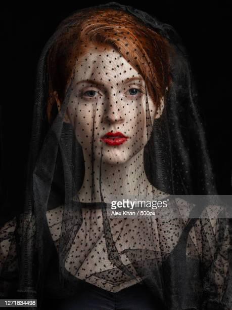 close-up portrait of young woman with veil over face against black background, petrogradka, russia - alleen één jonge vrouw stockfoto's en -beelden