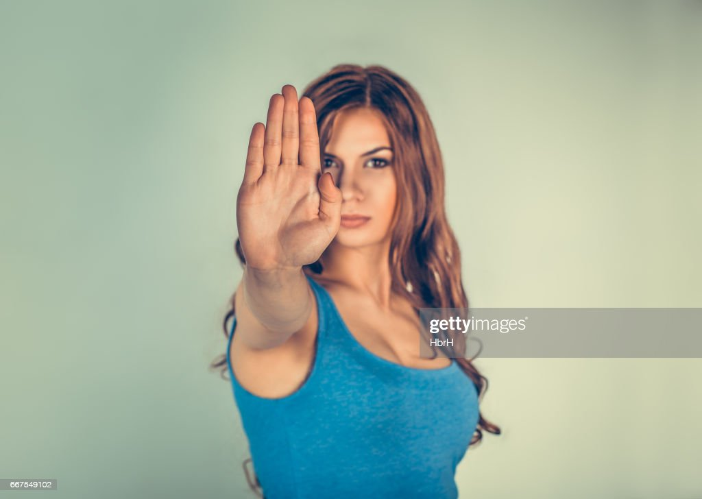 Closeup portrait young angry serious woman showing her denial No Stop talk to hand gesture with palm outward isolated green wall background Negative human emotion face expression feeling body language