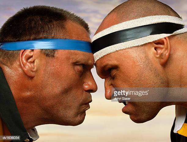 close-up profile of two rugby players head to head, scowling at each other - scrum stock-fotos und bilder