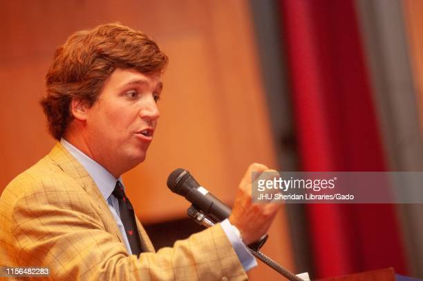 Close-up profile shot of political commentator Tucker Carlson, speaking into a microphone during a Milton S Eisenhower Symposium at the Johns Hopkins...