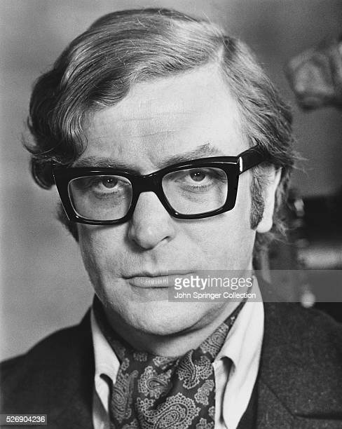 Closeup publicity handout of British actor Michael Caine shown hearing darkrimmed glasses and an ascot
