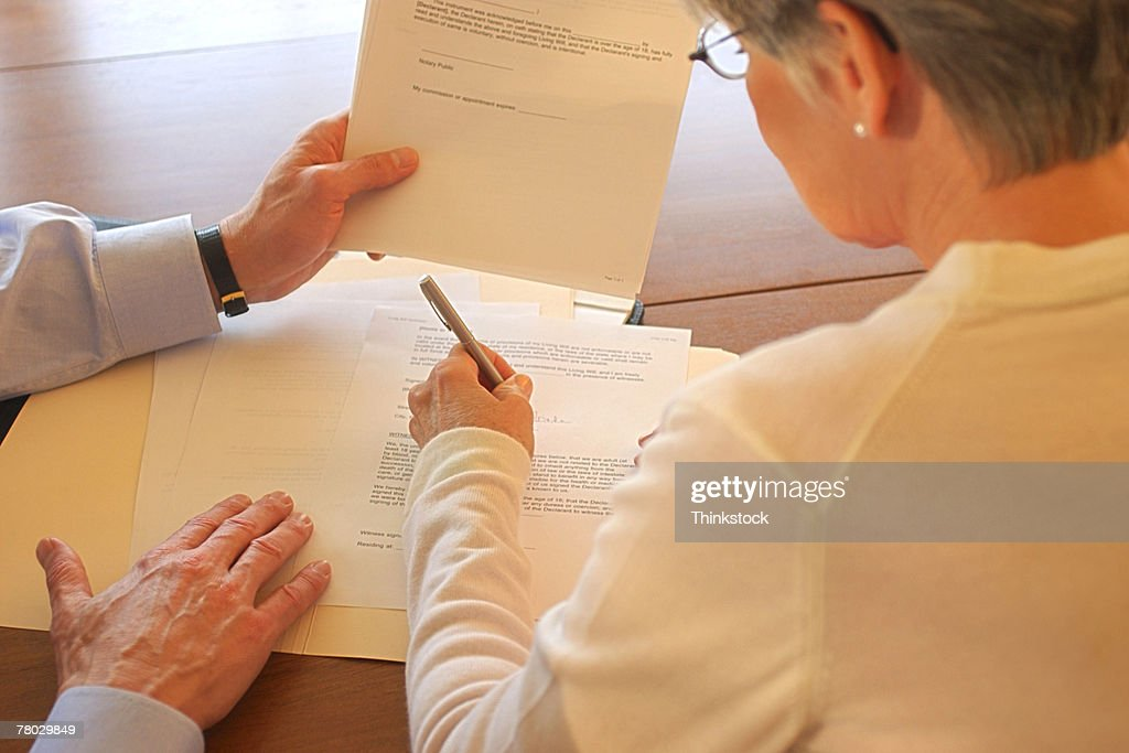 Closeup Rear View Of A Woman Signing Legal Documents At A Table - Signing legal documents