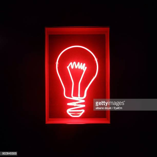 Close-up representation of neon bulb over black background