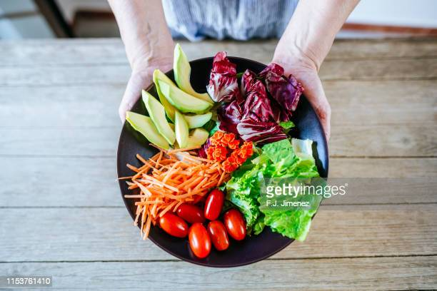 close-up salad of avocado, lettuce, tomato and carrot held by woman's hands - vegetarianism stock pictures, royalty-free photos & images