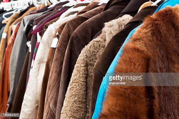 closeup secondhand winter coats and jackets hanging in shop - overcoat stock pictures, royalty-free photos & images
