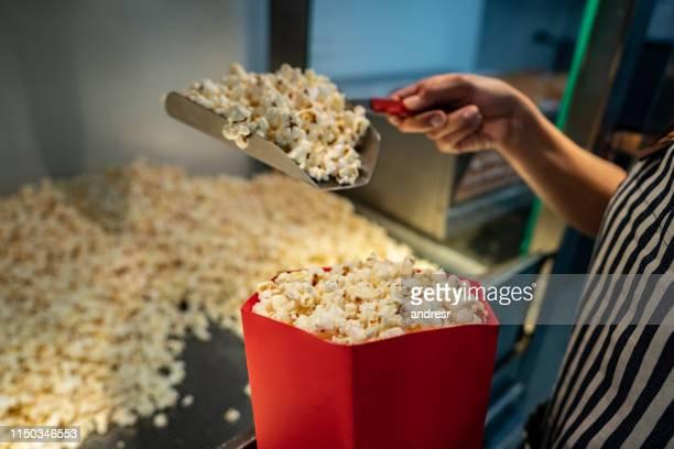 映画館での特約スタンドでポップコーンを提供するクローズアップ - ポップコーン ストックフォトと画像