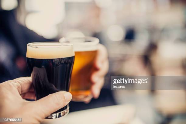close-up shot of a couple cheering with two different kind of beers, on the patio of a microbrewery - microbrewery stock photos and pictures