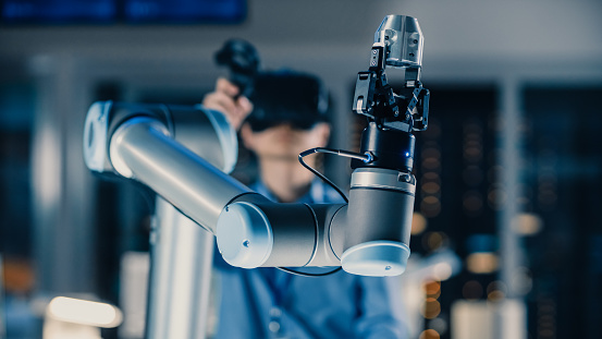 Close-up Shot of a Futuristic Robotic Arm Controlled by Professional Development Engineer with Virtual Reality Headset and Joysticks in a High Tech Research Laboratory with Modern Equipment 1193074366
