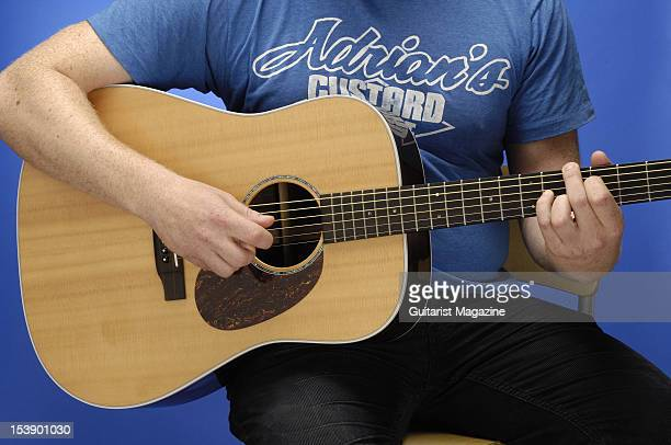A closeup shot of a man playing an acoustic guitar during a studio shoot for Guitarist Magazine June 10 2010