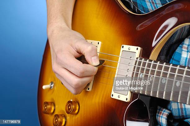 Close-up shot of a man's hand whilst playing a PRS electric guitar, during a studio shoot for Guitarist Magazine/Future via Getty Images, December...