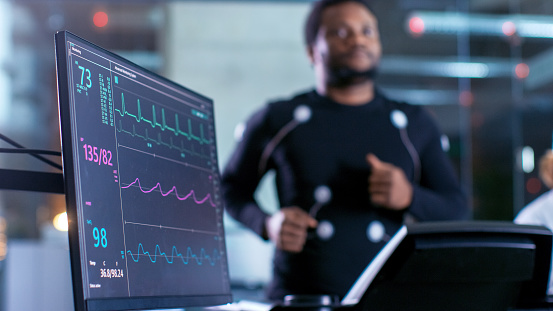 Close-up Shot of a Monitor With EKG Data. Male Athlete Runs on a Treadmill with Electrodes Attached to His Body while Sport Scientist Holds Tablet and Supervises EKG Status in the Background. 925425730