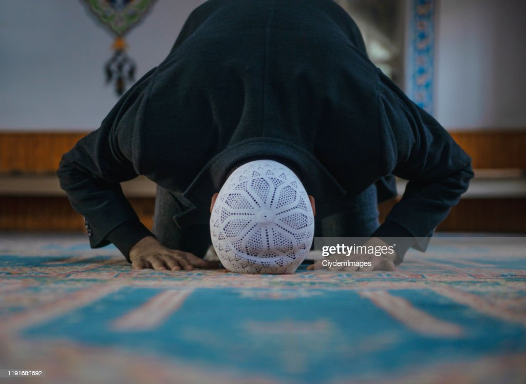 Close-up shot of a Muslim young man worshiping in a mosque : Stock Photo