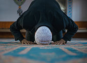 Close-up shot of a Muslim young man worshiping in a mosque