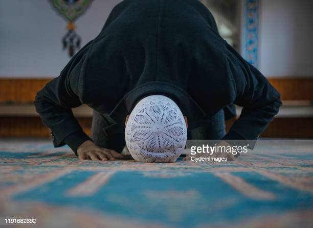 close-up shot of a muslim young man worshiping in a mosque - praying stock pictures, royalty-free photos & images