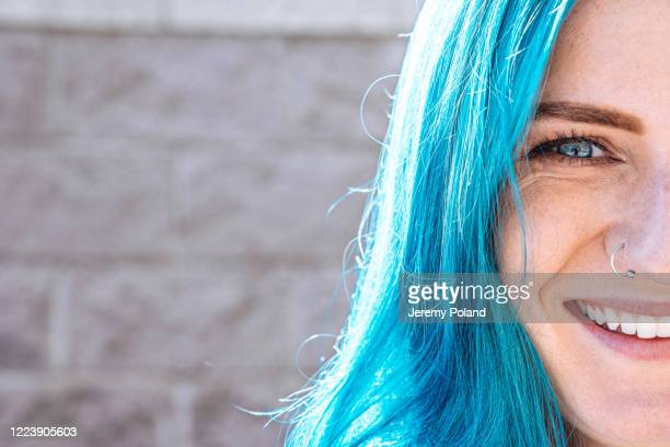 close-up shot of beautiful, unique, spunky, fashionable, young woman's blue eyes with fun cute teal blue-green dyed hair outdoors in the summer - blue hair stock pictures, royalty-free photos & images
