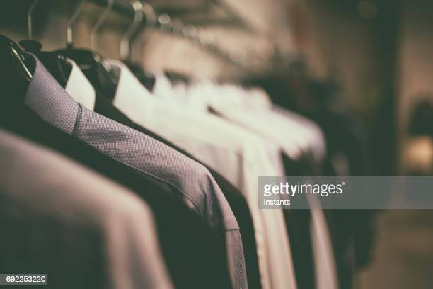 close-up shot of blue blouses with coathangers on a clothes rack. - men fashion stock photos and pictures