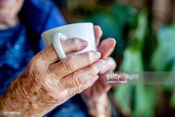 close-up shot of elderly senior caucasian person's hands holding a coffee or tea in a white ceramic mug indoors looking out the window in the summer - tea hot drink stock pictures, royalty-free photos & images