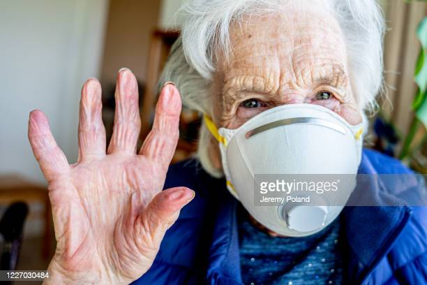 close-up shot of elderly senior caucasian woman smiling holding her hands up waving hello or goodbye wearing an n95 protective face mask to prevent the spread of covid sars ncov 19 coronavirus swine flu h7n9 influenza illness during cold and flu season - retirement community stock pictures, royalty-free photos & images
