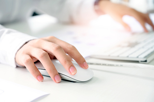 Closeup shot of female hand holding mouse and working with desktop computer. 1162160769