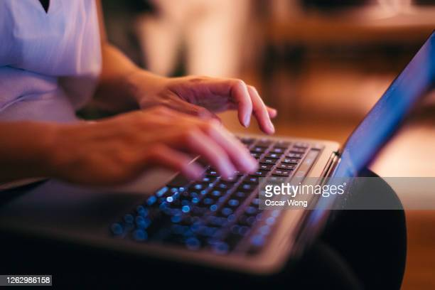 close-up shot of female hands typing on laptop keyboard, working late at home - the internet stock pictures, royalty-free photos & images