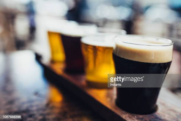 close-up shot of four kinds of beer on a microbrewery wooden palette, also known as a beer flight. - ale stock pictures, royalty-free photos & images