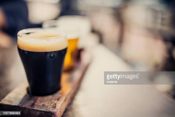 木製パレットで地ビール、ビール フライトとして知られているビールの 4 種類のクローズ アップ ショット。