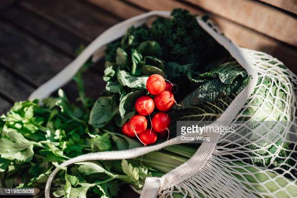 close-up shot of fresh organic vegetables in a reusable shopping bag on a wooden bench - crucifers stock pictures, royalty-free photos & images