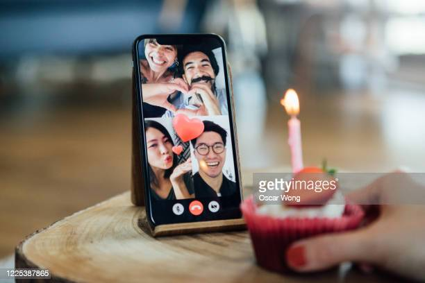 close-up shot of friends celebrating birthday on a video call using smart phone - mobile phone stock pictures, royalty-free photos & images