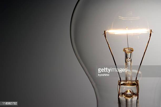 close-up shot of illuminated light bulb with copy space - light bulb stock pictures, royalty-free photos & images