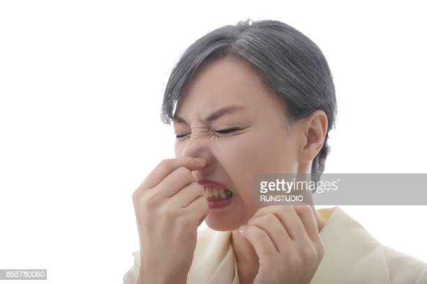 close-up shot of middle aged woman pinching her nose to avoid bad smell - ugly asian woman stock photos and pictures
