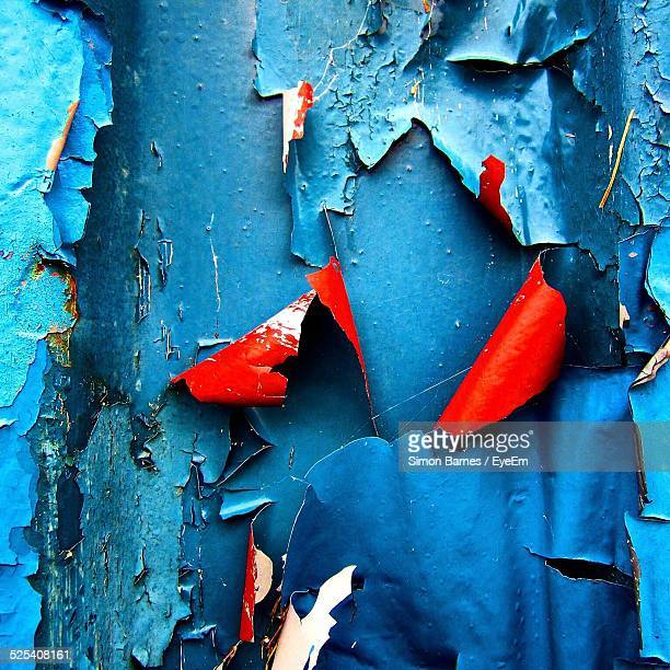 Close-Up Shot Of Patches Of Peeling Blue Paint With Red Undersides