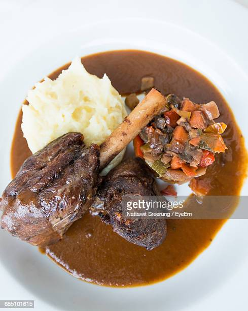 Close-Up Shot Of Roasted Lamp Shank With Mashed Potatoes On Table