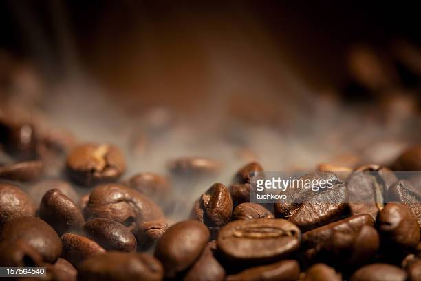 a close-up shot of steamy coffee beans - roasted coffee bean stock photos and pictures