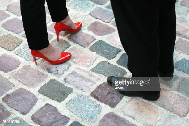 Closeup shot of the feet of a woman wearing red stilettos and feet of a man wearing smart shoes