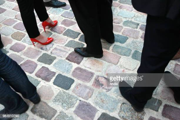 Closeup shot of the feet of a woman wearing red stilettos and feet of men wearing smart shoes