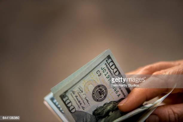 アメリカのドル札を保持している認識できない人のクローズ アップ ショット