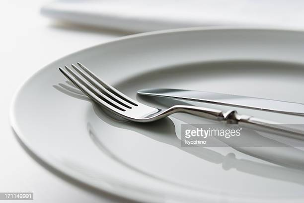 Close-up shot of white plate with fork and knife