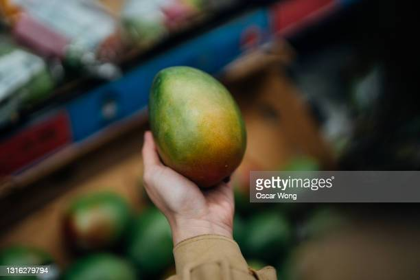 close-up shot of woman shopping fresh organic fruits in supermarket - growth stock pictures, royalty-free photos & images