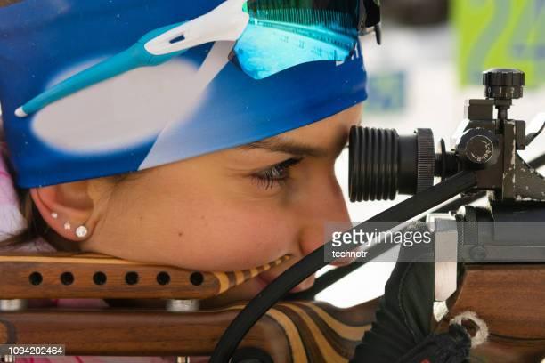 close-up schuss von jungen weiblichen biathlon konkurrent üben scheibenschießen - damen biathlon stock-fotos und bilder