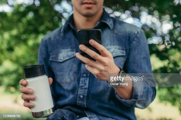 close-up shot of young man with a reusable coffee cup using smart phone - unrecognisable person stock pictures, royalty-free photos & images