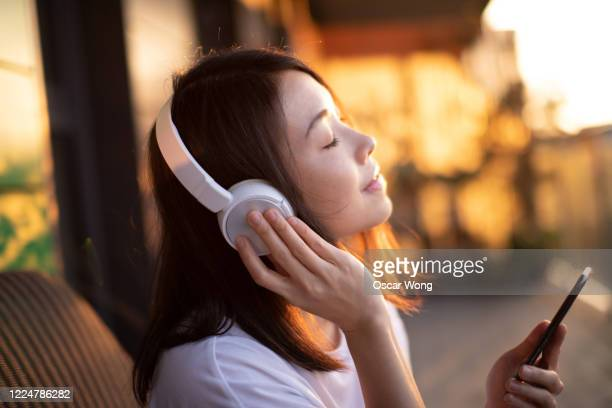 close-up shot of young woman enjoying music over headphones and using smart phone - mobile app stock pictures, royalty-free photos & images