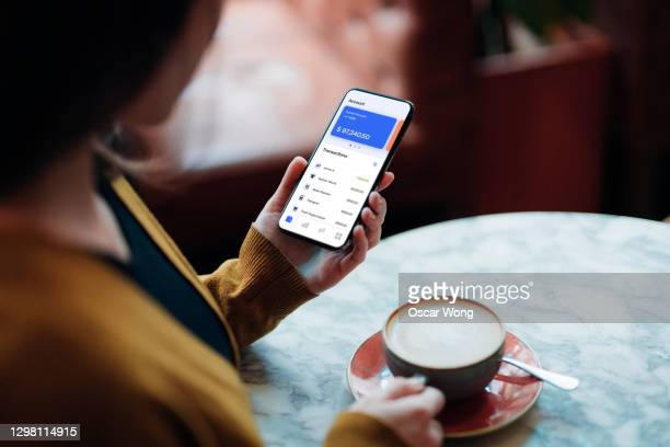 close-up shot of young woman managing bank account on smartphone at cafe - bank account stock pictures, royalty-free photos & images