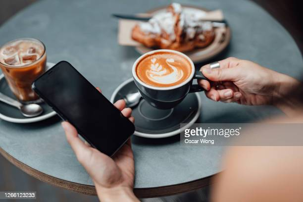 close-up shot of young woman using smart phone at cafe - unrecognisable person stock pictures, royalty-free photos & images