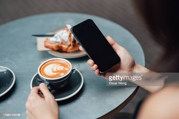 close-up shot of young woman using smart phone at cafe - looking over shoulder stock pictures, royalty-free photos & images