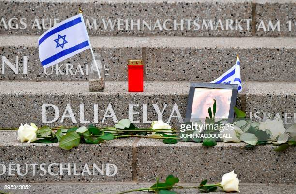 Closeup shows an Israeli flag and flowers left by relatives of Israeli tourist Dalia Elyakim at the memorial for the victims of last year's deadly...