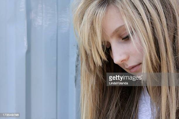 Close-up side view of a lonely teenage girl looking down